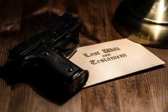 Pistol and testament on desk Stock Image