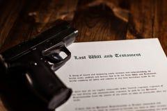 Pistol and testament on desk Stock Photos