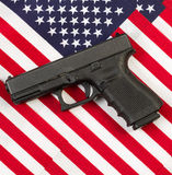 Pistol on top of American Flags Stock Images