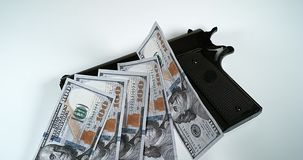 Pistol and 100 US Dollars Banknotes against White background, stock video
