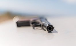 Pistol on white metal surface. Royalty Free Stock Photography