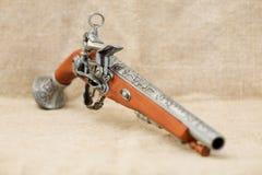 Pistola antiga na lona do fundo Fotografia de Stock Royalty Free