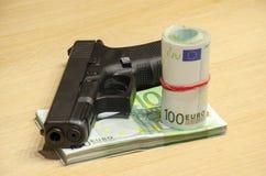 A pistola com balas fica atrás do dinheiro com retrocesso bllured da parede foto de stock royalty free