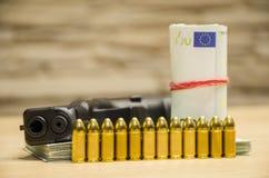 A pistola com balas fica atrás do dinheiro com retrocesso bllured da parede fotografia de stock royalty free