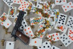 Pistola con le carte da gioco fotografie stock