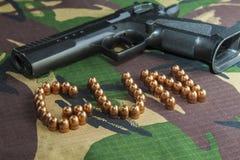 Pistola da arma de fogo no fundo da camuflagem das forças armadas Fotografia de Stock Royalty Free