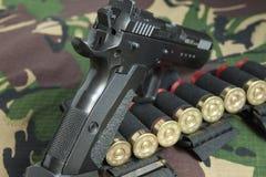 Pistola da arma de fogo no fundo da camuflagem das forças armadas Imagens de Stock Royalty Free