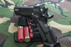Pistola da arma de fogo no fundo da camuflagem das forças armadas Fotografia de Stock