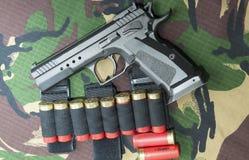 Pistola da arma de fogo no fundo da camuflagem das forças armadas Fotos de Stock Royalty Free