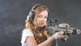 Pistola de sexo femenino de Airsoft que sostiene un rifle de asalto automático y que tiene como objetivo al enemigo metrajes