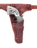 Pistola del cowboy del giocattolo in custodia per armi isolata. immagini stock libere da diritti
