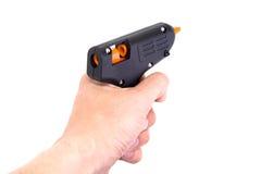 Pistola della colla in una mano isolata. Fotografia Stock