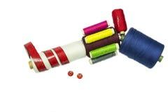 Pistola della pistola dalle bobine di cucito con i bottoni rossi Fotografia Stock Libera da Diritti