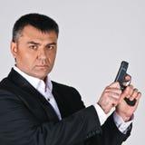 Pistola della tenuta dell'uomo d'affari Fotografia Stock Libera da Diritti