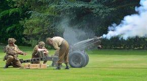 Pistola di campo di seconda guerra mondiale che è artiglieri licenziati che portano le uniformi Immagine Stock