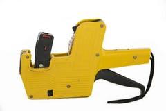 Pistola di plastica gialla dell'etichetta di prezzi su bianco Immagine Stock