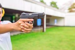 Pistola do alvo da aplicação da lei pela mão dois na escala de tiro da academia Imagem de Stock