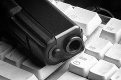 Pistola e computer Immagini Stock