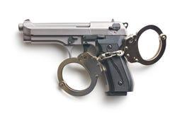 Pistola e manette Immagini Stock