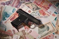 Pistola e soldi Immagini Stock