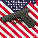 Pistola encima de banderas americanas Imagenes de archivo