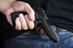 Pistola nascosta nel lato posteriore delle mani all'uomo in blue jeans immagine stock