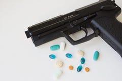 Pistola negra que miente al lado de un surtido de drogas y de píldoras fotos de archivo