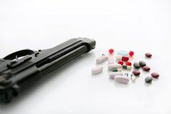 Pistola o pillole due opzioni al suicidio Fotografia Stock Libera da Diritti