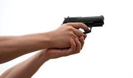 Pistola preta em uma mão no branco Fotos de Stock