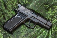 Pistola semiautomática no fundo da camuflagem do pixel Imagens de Stock Royalty Free