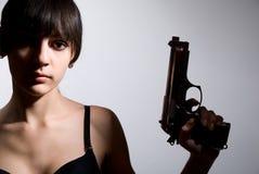 Pistola sexy della tenuta della donna su gray immagini stock