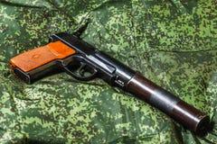 Pistola silenciada semiautomática en fondo del camuflaje del pixel Fotografía de archivo