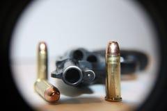 Pistola sulla tabella con i richiami Fotografia Stock