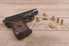 Pistola traumático com balas e cartucho na superfície de madeira, grupo imagem de stock