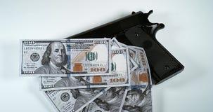 Pistola y 100 dólares de EE. UU. de billetes de banco contra el fondo blanco, almacen de metraje de vídeo