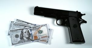Pistola y 100 dólares de EE. UU. de billetes de banco contra el fondo blanco, almacen de video