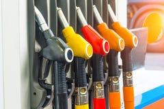 Pistolas de la gasolina que aprovisionan de combustible los coches en la estación, contra el contexto de una rueda del camión imagenes de archivo