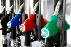 Pistolas vermelhas verdes do combustível do preto azul na estação do combustível Imagem de Stock