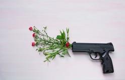 Pistole auf hölzernem Hintergrund mit Blumen Krieg und Frieden lizenzfreies stockfoto