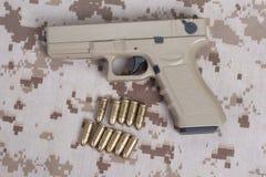 Pistole auf Tarnungsuniform lizenzfreies stockbild