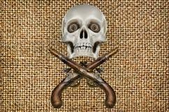 Pistole e modello antichi del cranio su fondo del panno Fotografia Stock
