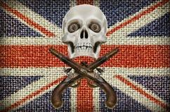 Pistole e modello del cranio su fondo della bandiera di Britannici Fotografie Stock
