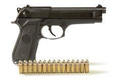 Pistole und fünfzehn Gewehrkugeln Lizenzfreie Stockbilder