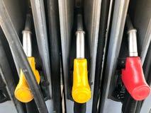 Pistole variopinte di riempimento ad una stazione di servizio per il rifornimento di carburante dell'automobile con combustibile, fotografia stock
