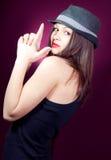 Pistolegeste u. lächelnde schöne junge Frau Stockfoto