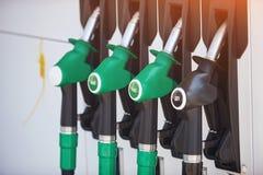 Pistolen die van benzine auto's van brandstof voorzien bij de post Geen mensen stock afbeelding