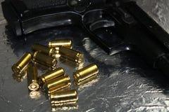 Pistolengewehrdetail mit goldener Messingmunition auf glänzendem silbernem Schreibtisch Lizenzfreie Stockfotografie