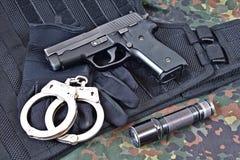 Pistolet avec des menottes, des gants et la lampe-torche sur le gilet et l'habillement tactiques de camouflage images stock