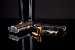 Pistolet 1911 avec des munitions sur le noir Images stock