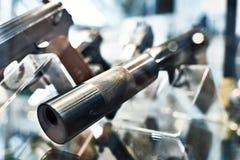 Pistolet avec le silencieux dans la fenêtre de boutique Image stock